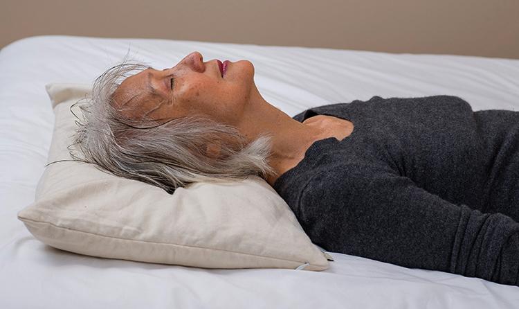 Женщина спит на гречневой подушке