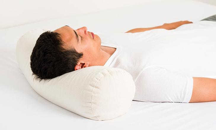 Мужчина спит на подушке из гречки