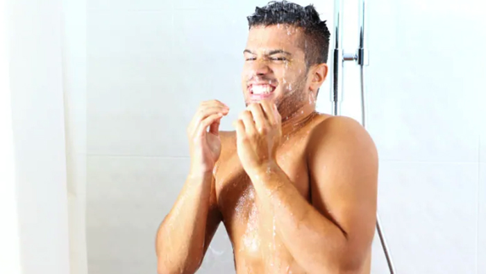 Мужчина принимает холодный душ