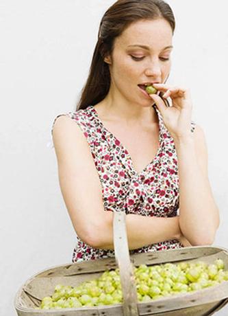 Женщина кушает крыжовник